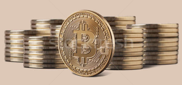 Single bitcoin coin standing in front of stacks of coins Stock photo © artjazz
