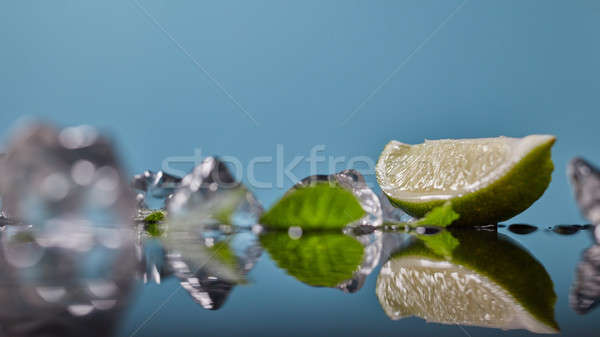 Slice of lime wedge, ice and mint isolated on blue background Stock photo © artjazz