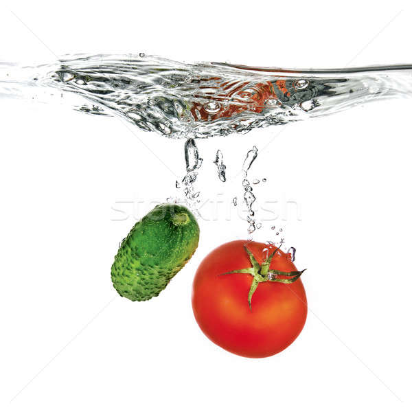 red tomato and green cucumber dropped into water isolated on white  Stock photo © artjazz