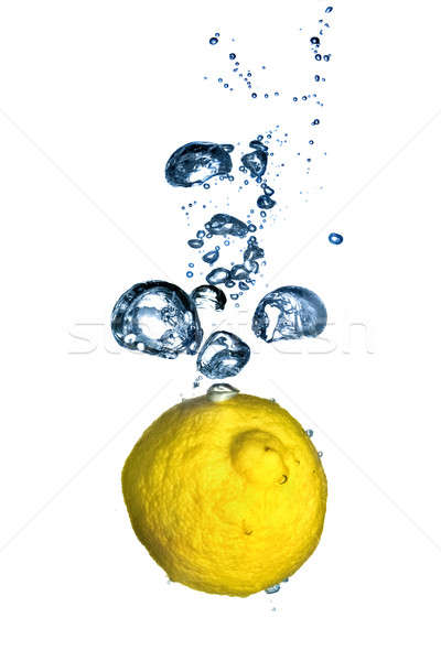 Fresh lemon dropped into water with bubbles isolated on white Stock photo © artjazz