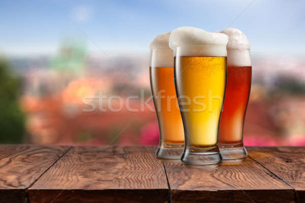 Glasses of different beer on wooden table against Prague Stock photo © artjazz