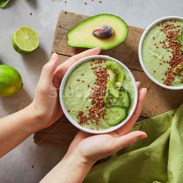 In the female hands of a bowl with green healthy smoothies Stock photo © artjazz