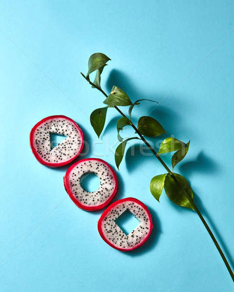 Composition of round pieces of pitaya and green branches on a blue background Stock photo © artjazz