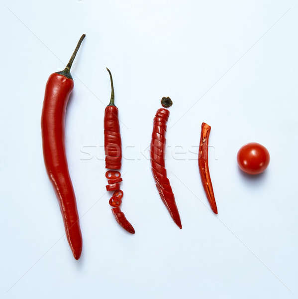 sliced chilli cayenne pepper with tomato on a gray background, top view Stock photo © artjazz