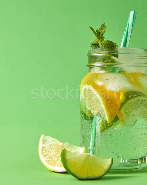 Fresh cold homemade cocktail on a green background. Citrus fruits slices of lemon and lime, ice, wat Stock photo © artjazz