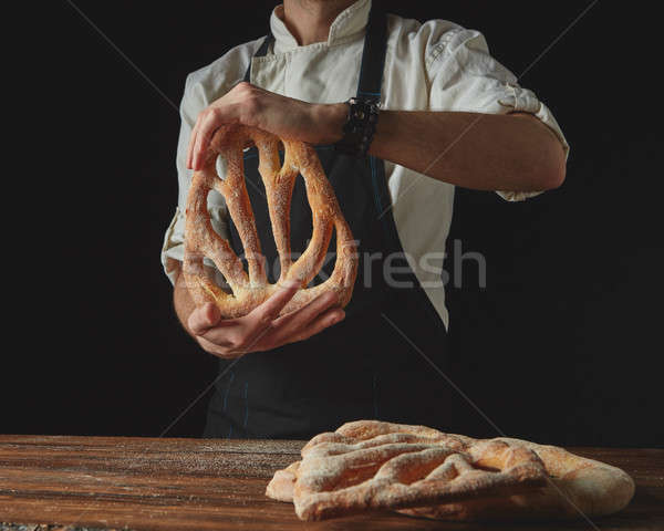 on background of wooden brown table, men's hands hold bread foug Stock photo © artjazz