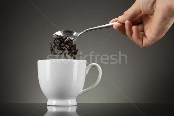 tea pour out into white cup on grey Stock photo © artjazz