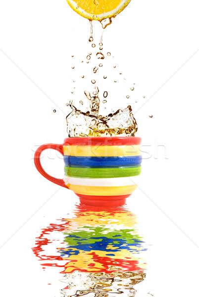 Lemon juice and splash of tea in color cup with reflection Stock photo © artjazz