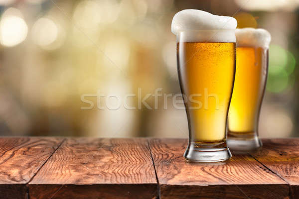 Two Glass of beer on wooden table Stock photo © artjazz