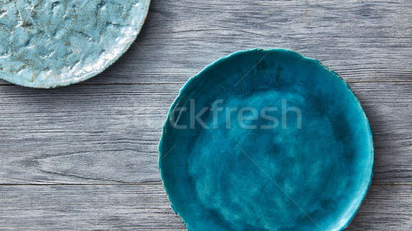 Two porcelain blue bowls on a gray wooden table. Multi-colored ceramic vintage handmade dishes. Top  Stock photo © artjazz