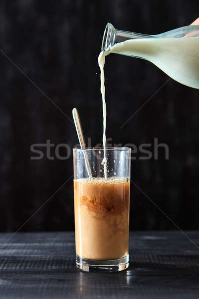 In freshly prepared coffee in a transparent glass pour milk on a black wooden table. Delicious morni Stock photo © artjazz