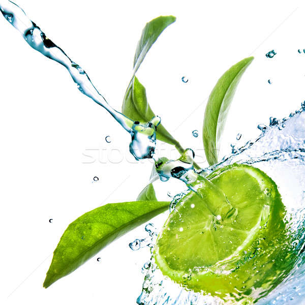 Stock photo: water drops on lime with green leaves isolated on white