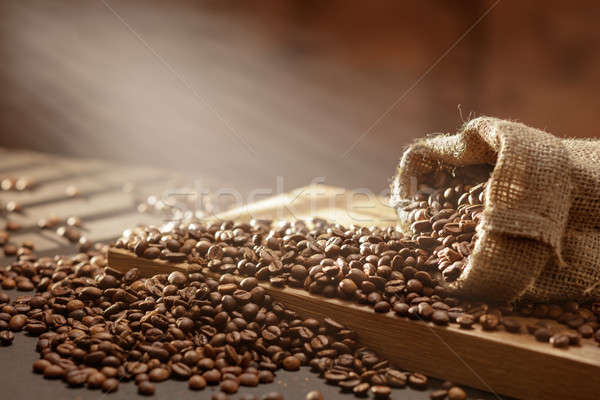 spilled coffee beans in bag on wood Stock photo © artjazz