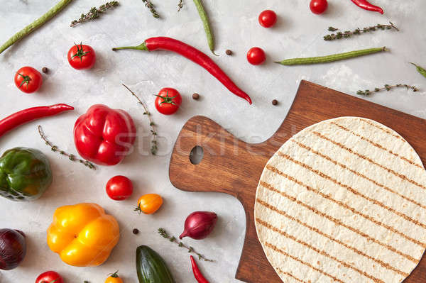 cooking burrito with vegetable on a wooden board on a gray concrete background Stock photo © artjazz