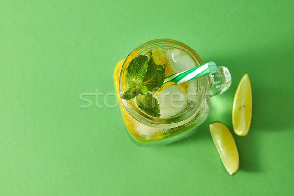 Refreshing natural non-alcoholic cocktail in glass jar with ice cubes, slices of lime and lemon, spr Stock photo © artjazz