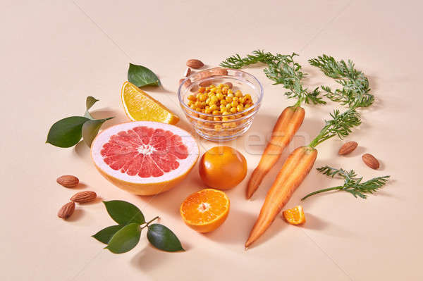 Natural freshly picked fruits- citrus fruits, carrots, sea buckthorn berries on an orange paper. Stock photo © artjazz