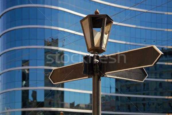 Blank signpost with ancient lamp against business building Stock photo © artjazz