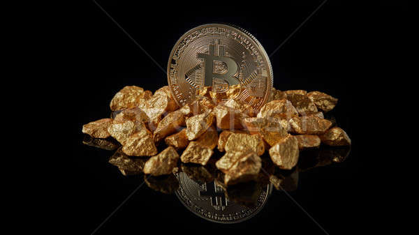 Bitcoin coin cryptocurrency and mound of gold nuggets on a black reflective background Stock photo © artjazz