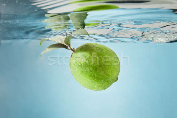 Lime falls into the water creating splashes on the water Stock photo © artjazz