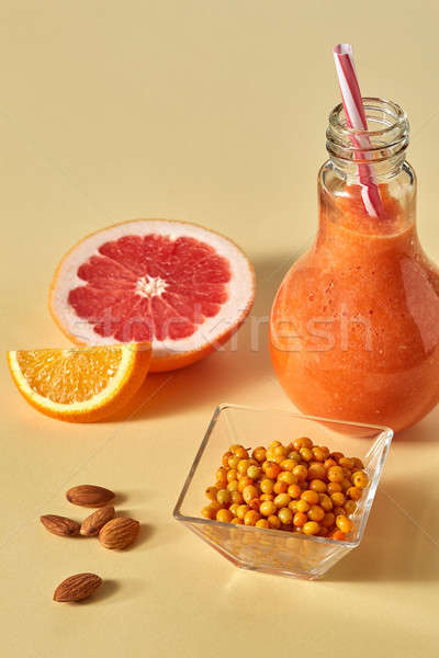 Vitamin drink with sea buckthorn, almonds, orange and grapefruit in glass on an orange paper backgro Stock photo © artjazz