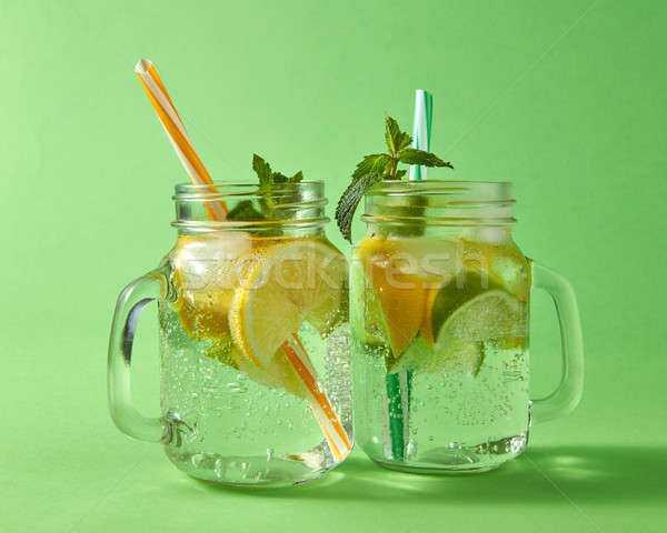 Citrus fruits slices of lemon and lime, ice, water and plastic straws in the glass on a green backgr Stock photo © artjazz