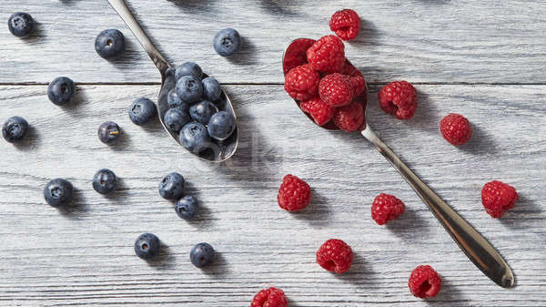 Two spoons with red juicy ripe berries - raspberry and blueberry and around them on a gray wooden ba Stock photo © artjazz