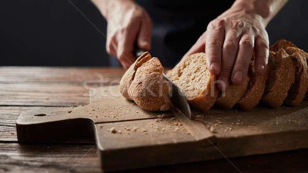 man cutting fresh bread on wooden table Stock photo © artjazz
