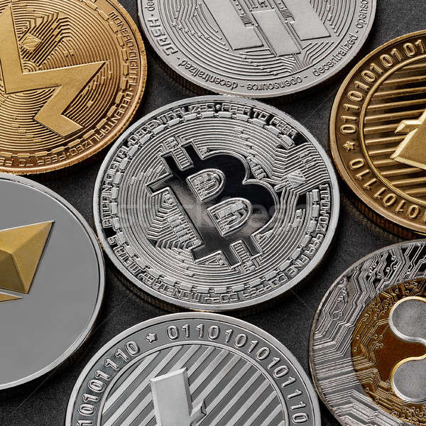 Different coins of crypto currency on a black background. Business concept. Stock photo © artjazz