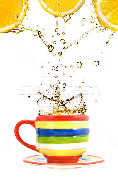 three lemons, color cup and splash of tea isolated on white Stock photo © artjazz
