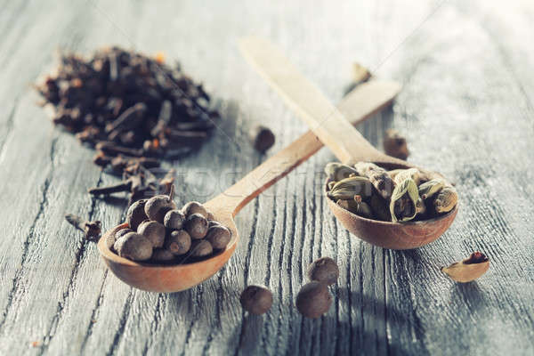 Nutmeg, clove and allspice in old spoon on wooden table Stock photo © artjazz