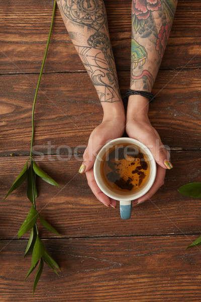 Kobiet ręce hot herbaty tatuaże Zdjęcia stock © artjazz
