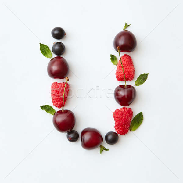 Fresh berries pattern of letter U english alphabet from natural ripe berries - black currant, cherri Stock photo © artjazz