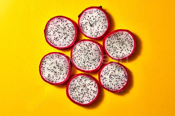 Flat lay view of background from round slices of Dragon fruit or Pitaya on a yellow background. Stock photo © artjazz