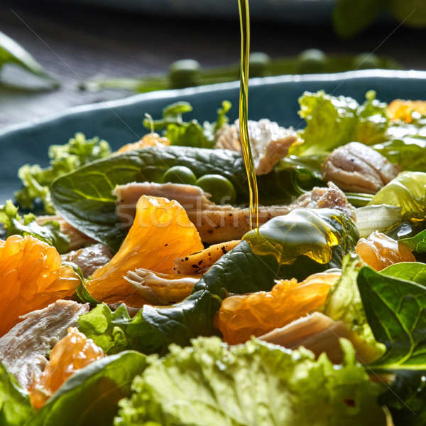 Stock photo: Close-up of steam of olive oil pours into the salad with natural green vegetables, chicken pieces, o