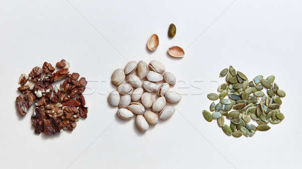 Mix of assorted natural nuts - pistachios, walnuts, pumpkin seed . Organic natural pattern on a whit Stock photo © artjazz