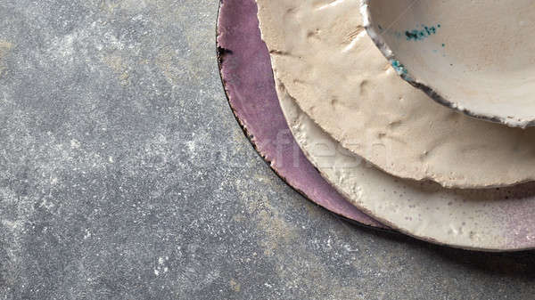 Vintage painted glazed plates, bowls handmade on gray concrete table with free space ror text. Stock photo © artjazz