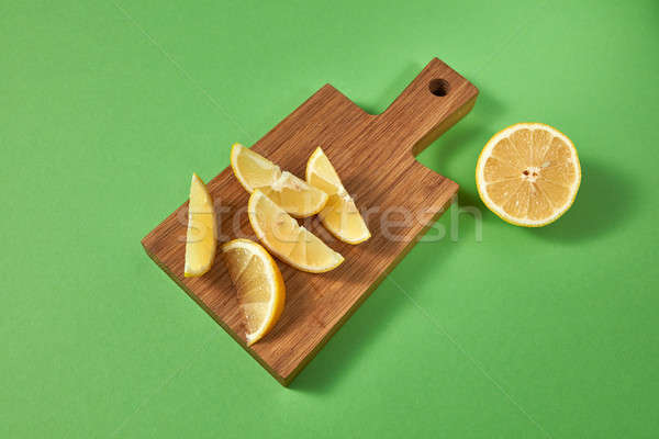 Half and slices of fresh tropical yellow lemon on a wooden cutting brown board. View from above. Cit Stock photo © artjazz