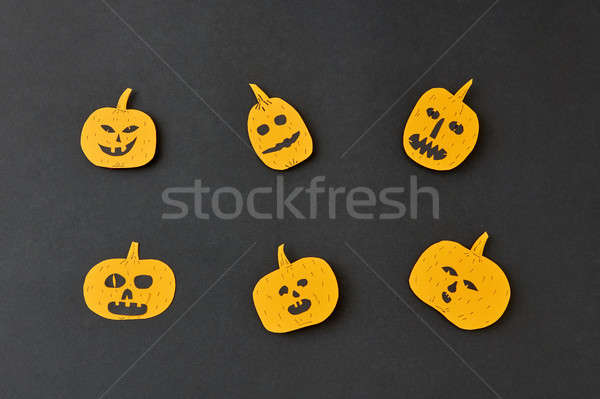 Handcraft decoratide pattern from flying smiling and laughing yellow pumpkins on a black background. Stock photo © artjazz