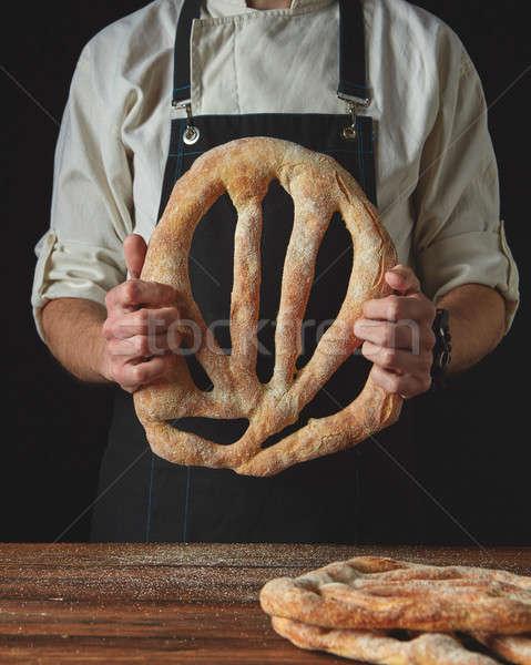 Baker's hands hold fougas bread Stock photo © artjazz