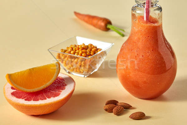 Citrus vegetable smoothies with almonds and sea-buckthorn in a glass on a yellow paper background Stock photo © artjazz