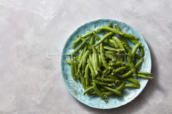 Stock photo: Natural organic green peas in sticks on a blue ceramic plate on a gray marble kitchen table. Top vie
