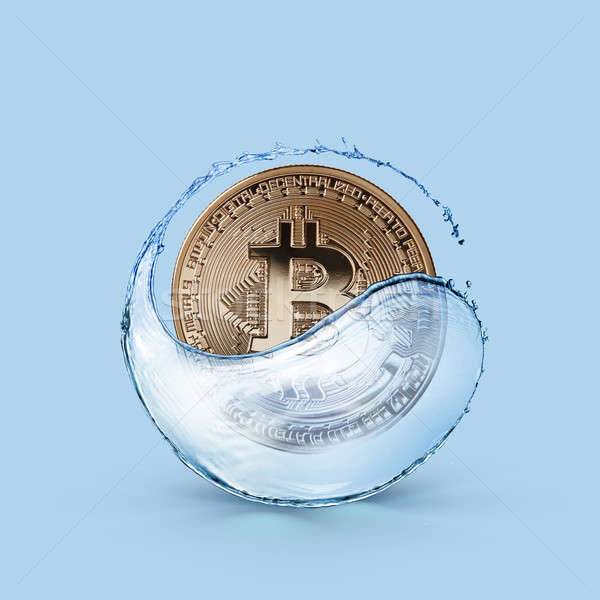 Gold coin bitcoin in a splash of water on a blue background Stock photo © artjazz