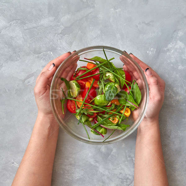 Female hands hold a plate with salad Stock photo © artjazz