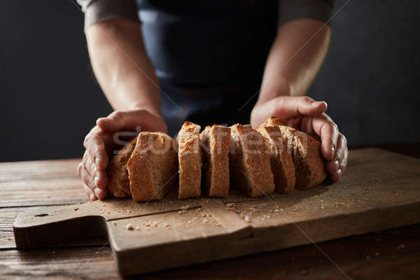 Fresh slice home bread in male's hands on wooden table Stock photo © artjazz