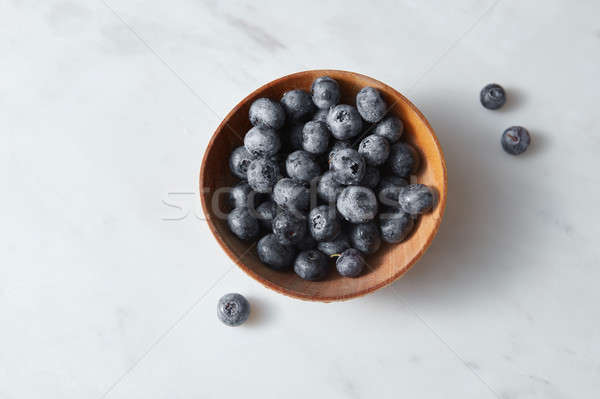 Organic freshly picked blueberry in a wooden bowl on a white kitcen table. Copy space. Stock photo © artjazz
