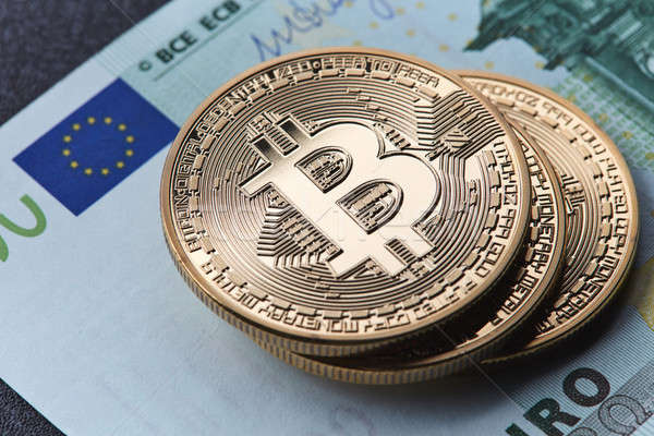 Stack of gold coins bitcoin stack on a euro bill Stock photo © artjazz