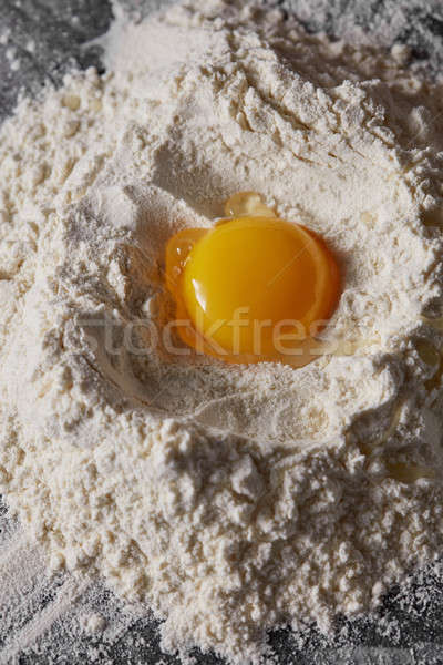 Raw egg and flour on the kitchen table, staged cooking dough Stock photo © artjazz