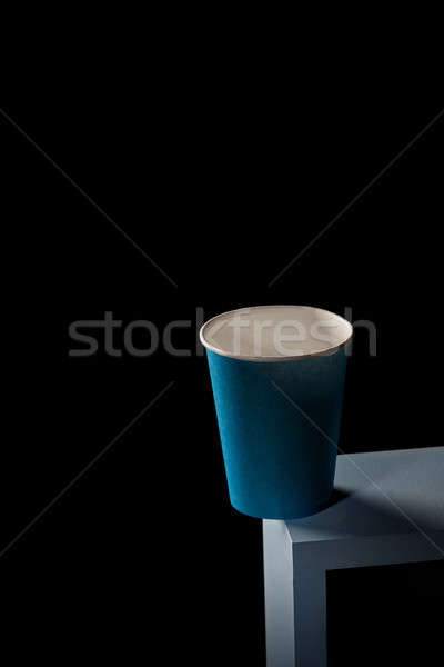 A blue paper cup stands on the edge of a blue square frame on a black square background. Stock photo © artjazz