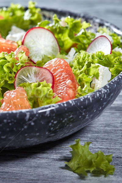 Delicious natural vegetarian salad with fresly picked vegetables, lettuce, citrus fruit, cheese in a Stock photo © artjazz