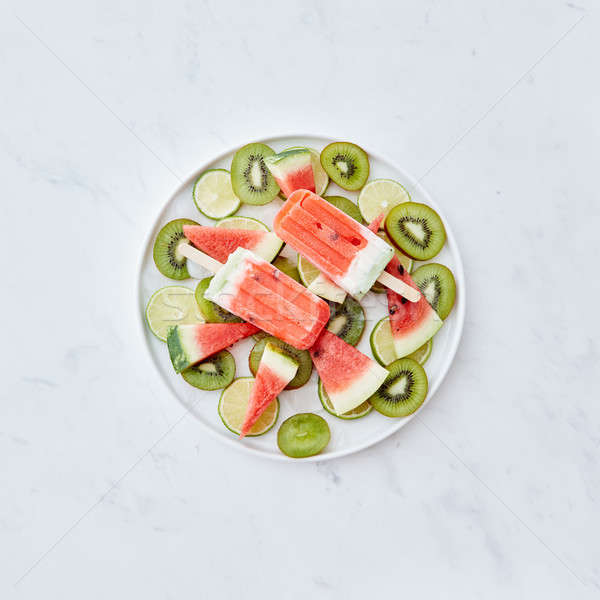 Multicolored berry frozen smoothies lolly with pieces of kiwi, lime, watermelon and ice cubes in a p Stock photo © artjazz